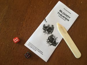 A copy of the folded trifold sits on a table with dice and a bone folder.